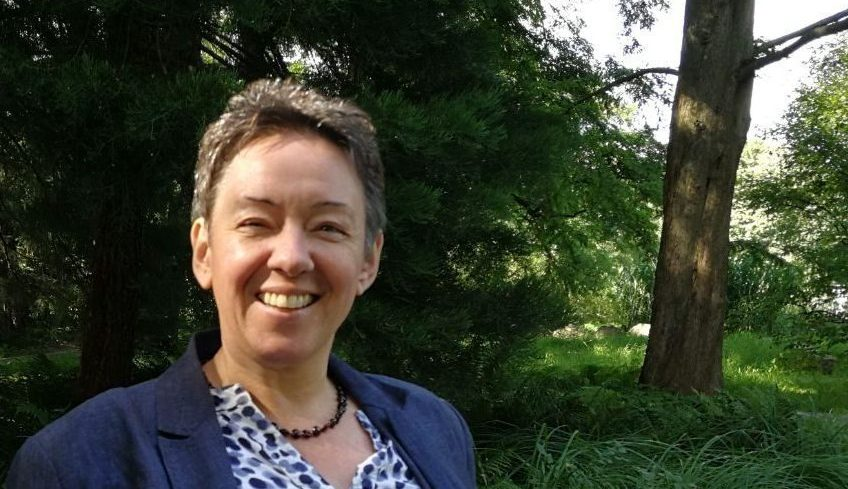 Foto zeigt Elisabeth Jaskolla lächelnd. Sie steht im Wald. Im Hintergrund sind Bäume zu sehen.