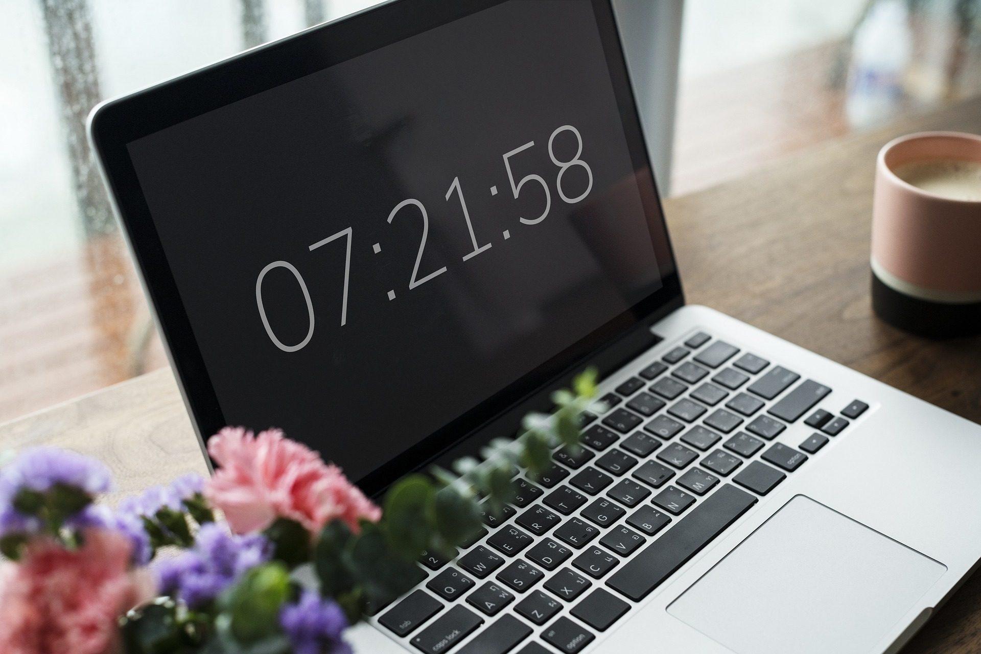 Laptop steht auf einem Tisch, daneben eine Tasse und ein Blumenstrauß in den Farben rose und lila